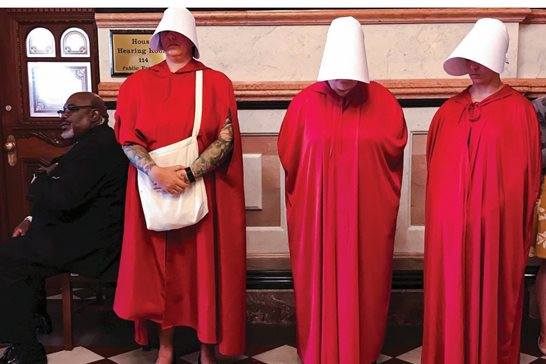 "Women dressed as Handmaids, characters from Margaret Atwood's dystopian novel ""The Handmaid's Tale,"" stand by as House Democrats meet on the other side of the door to discuss the future of the Reproductive Health Act on Wednesday in the Illinois statehouse."