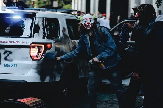 A photo from a federal criminal complaint filed Tuesday against Timothy O'Donnell shows a man in a clown mask setting a Chicago police vehicle on fire along the 200 block of North State Street during protests on Saturday. O'Donnell admitted to investigators after his arrest Tuesday that he was the person photographed. He faces federal arson charges.