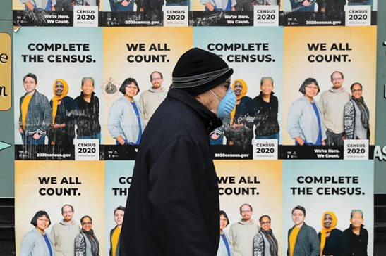 A man wearing a mask walks past posters encouraging participation in the 2020 Census in Seattle. A delay in census data is scrambling plans in some states to redraw districts for the U.S. House and state legislatures. The Census Bureau has said redistricting data that was supposed to be provided to states by the end of March won't be ready until August or September.