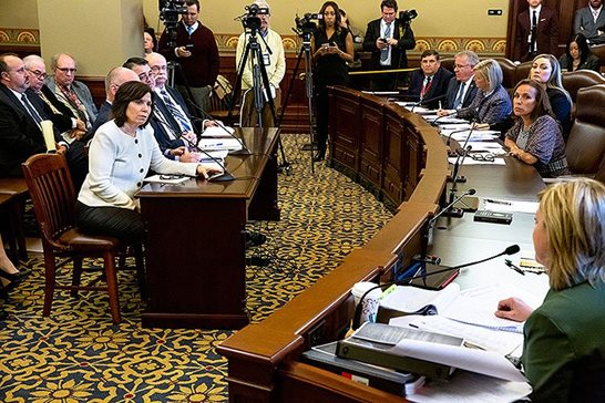 Dr. Carla Knorowski (in white jacket at table), chief financial officer of the Abraham Lincoln Presidential Library and Museum Foundation, answers questions Tuesday at the Illinois Capitol from Rep. Jeanne Ives, R-Wheaton, during a House Tourism Committee hearing looking into the value of a Lincoln collection purchased by the foundation and the loan to pay for it after questions have been raised about the historical authenticity of a stovepipe hat believed to have been owned by Abraham Lincoln.