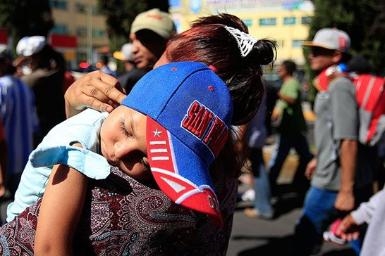 A sleeping Honduran girl is carried as a group of Central American migrants, representing the thousands participating in a caravan trying to reach the U.S. border, undertake an hours-long march to the office of the United Nations' humans rights body in Mexico City on Thursday. Members of the caravan demanded buses Thursday to take them to the U.S. border, saying it is too cold and dangerous to continue walking and hitchhiking.