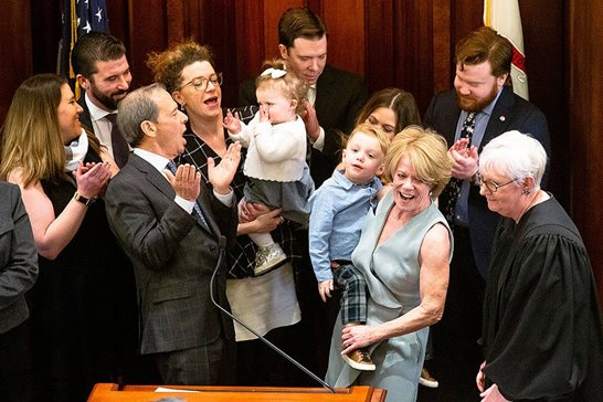 Joined at the dais by staff, relatives and Supreme Court Justice Mary Jane Theis (far right), Illinois Senate  President John J. Cullerton (center) coaxes his granddaughter Edie to blow kisses after he was sworn in for another leadership term Wednesday at the Capitol.