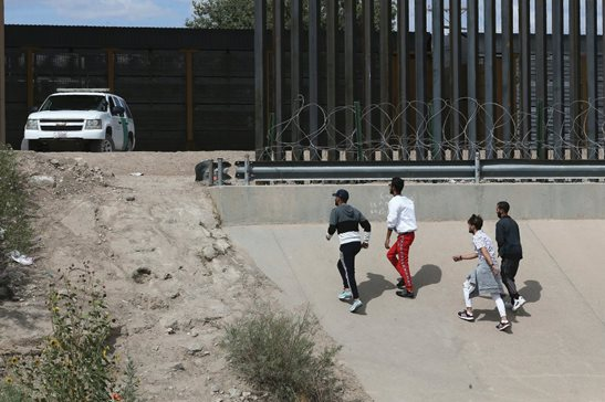 A group of asylum seekers cross the border between El Paso, Texas, and Juarez, Chihuahua, Mexico, in July. The nation's high court issued an order Wednesday allowing enforcement of new rules that generally preclude asylum applications from most Central American migrants.