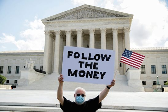 "Bill Christeson holds up a sign that reads ""Follow the Money"" outside the U.S. Supreme Court on Thursday in Washington. The Supreme Court ruled that the Manhattan district attorney can obtain Trump tax returns while not allowing Congress to get Trump tax and financial records, for now, returning the case to lower courts."